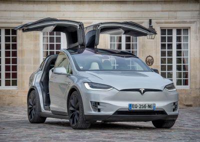 Vue extérieure d'une Tesla Model X, de face, grise métallisée, portes papillon relevées
