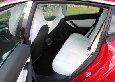 banquette arrière, blanche, de la Tesla 3 rouge