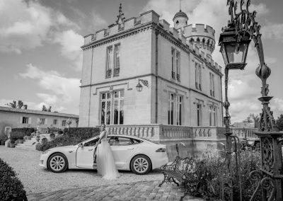 La mariée rentre dans sa Tesla garée devant un chateau