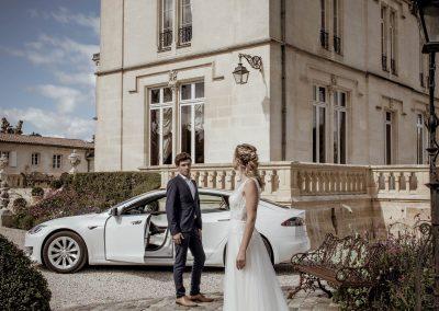 Un couple dans le parc du chateau devant une Tesla S