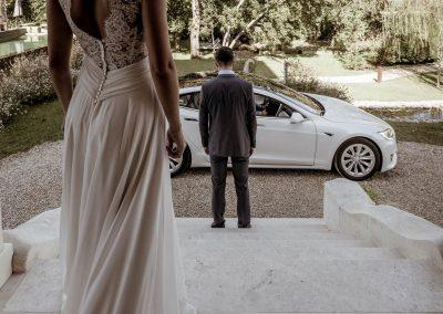 Au premier plan, le dos de la mariée. Devant elle son époux en costume gris. En bas des marches : une Tesla S