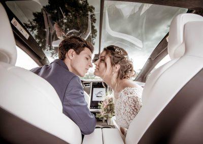 Un couple sapprête à s'embrasser dans leur Tesla
