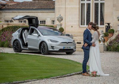 Un couple s'embrasse dans le parc du chateau devant une Tesla X