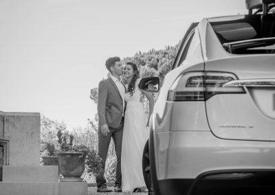 Un couple de mariés derrière une Tesla X porte papillon ouverte
