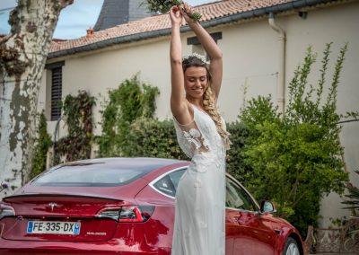 Une mariée devant une Tesla 3 rouge