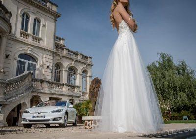 Focus sur la robe de la mariée, avec une Tesla S blanche en fond