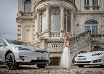 Une mariée devant le perron d'un chateau au bord duquel sont garées deux Tesla